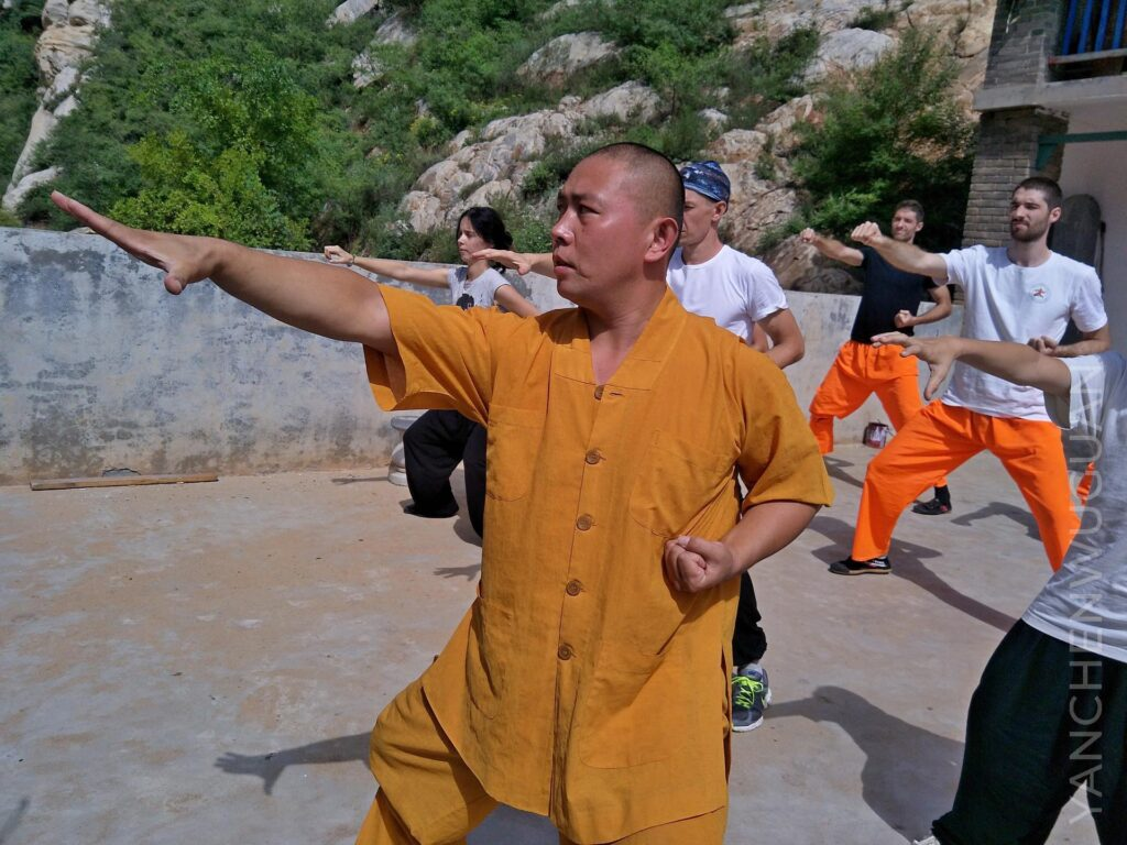 a group of foreigners practice qigong with a master. eight pieces of brocade kung fu master in monastic robes orange