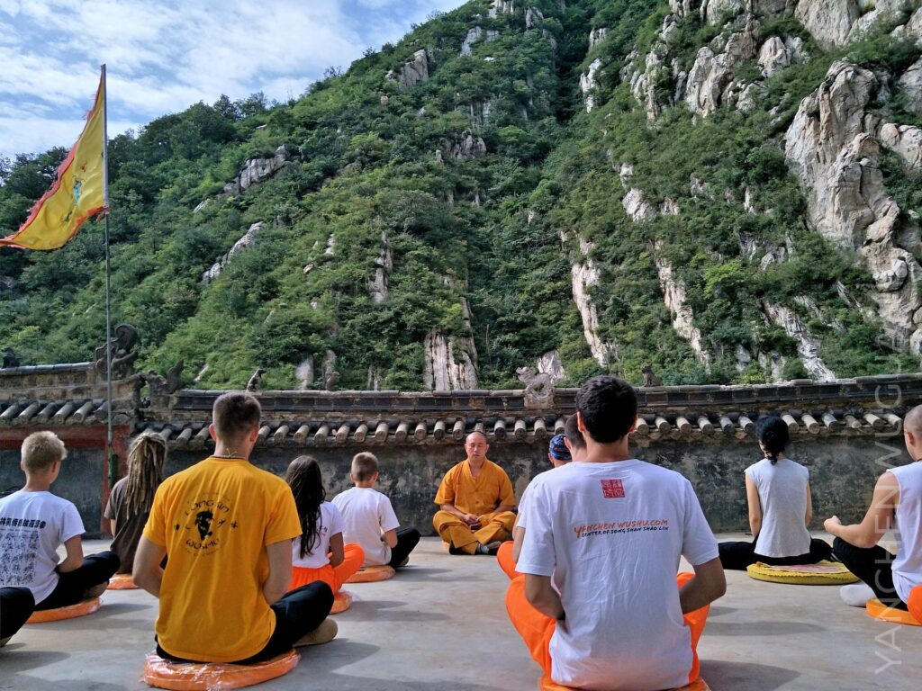 a group of foreigners meditate with a master