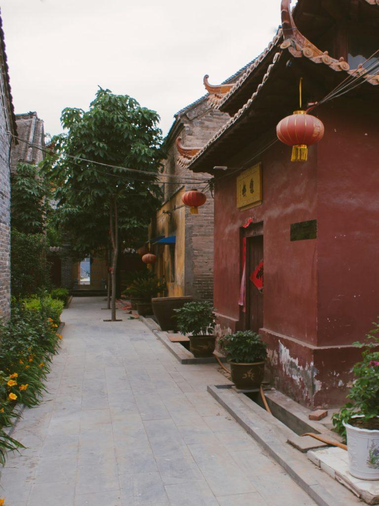A narrow street in the territory of a Chinese temple of a monastery red walls and a red lantern green bushes
